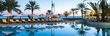 Pool at dusk at Constantinou Bros Athena Royal Beach Hotel