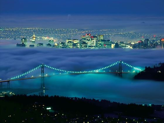 Lions Gate Bridge in fog and Vancouver skyline at night