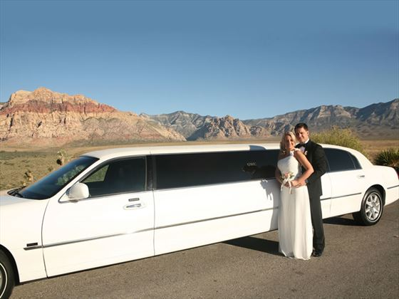 Bride & Groom with their white, stretch limousine