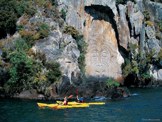 Kayaking alongside Maori carvings at Mine Bay, Lake Taupo