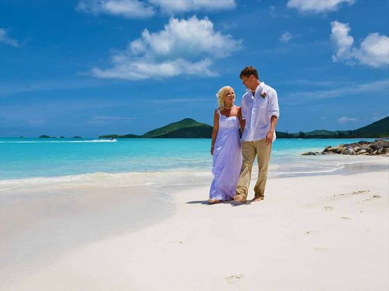 Wedding couple with glittering coastline and crystal blue waters