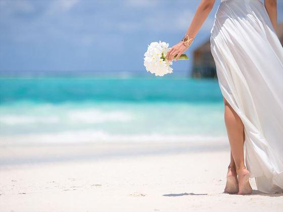 Bride walking along the beach at LUX* South Ari Atoll