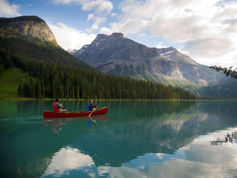 canoeing emerald lake with mountain views
