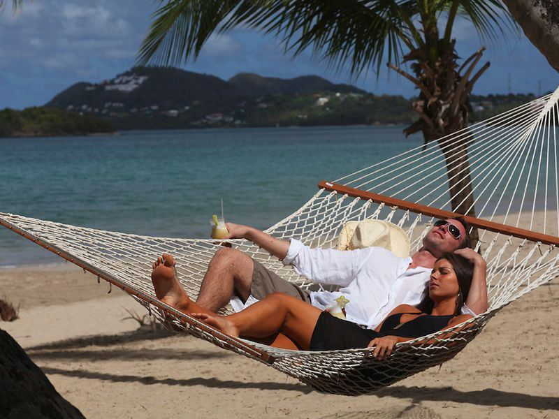 couple relax on a beach hammock at rendezvous