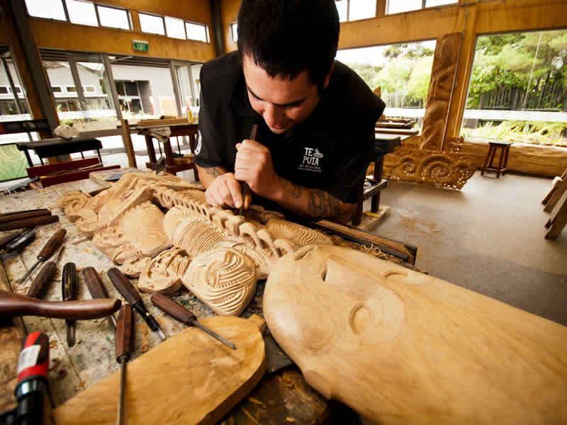 maori man carving wood rotorua new zealand