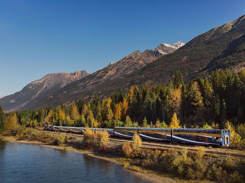 rocky mountaineer travelling along the waters edge on journey through the clouds